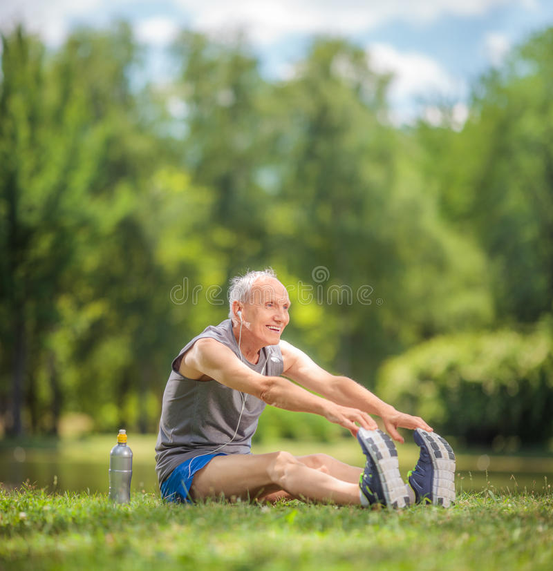 Senior doing stretching exercises in park stock photos