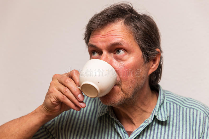 Senior is drinking a cup of coffee. Senior adult is drinking a cup of coffee stock image