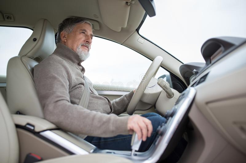 Senior drive driving his modern car, going in reverse stock images