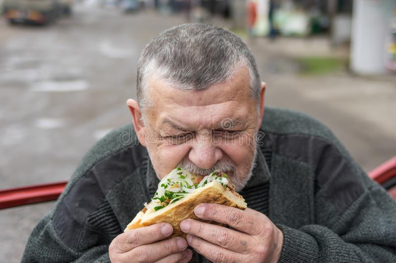 Senior driver eating lyulya kebab in lavash near his car. Caucasian senior driver eating lyulya kebab in lavash near his car royalty free stock images