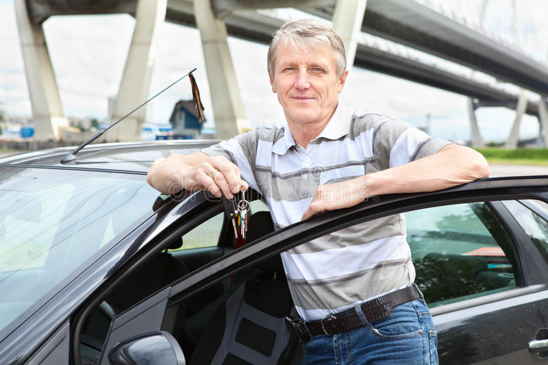 Senior driver with ignition key near car. Happy Caucasian mature driver with car key standing near own land vehicle stock images