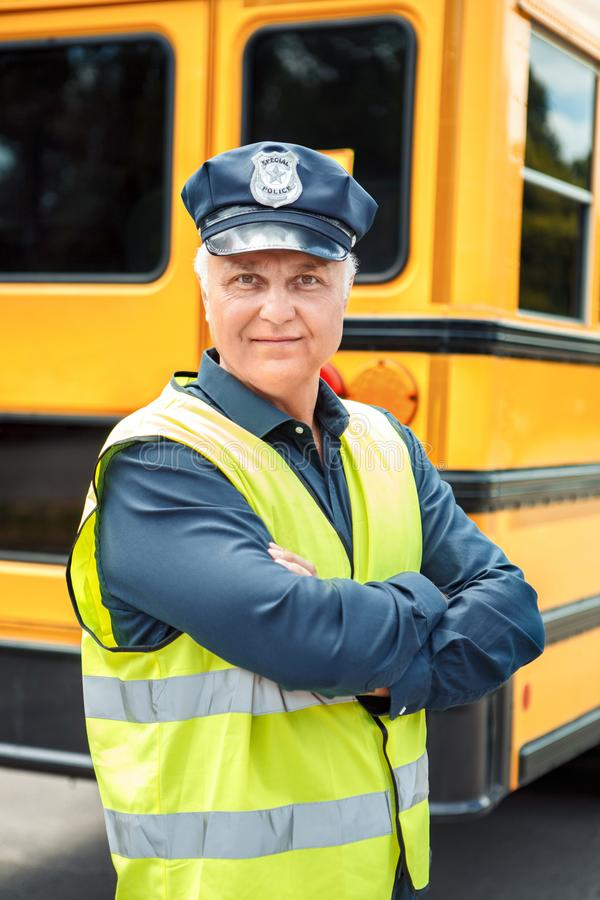 Senior driver standing near school bus crossed arms smiling confident. Senior driver weaering uniform standing near school bus crossed arms looking camera royalty free stock image