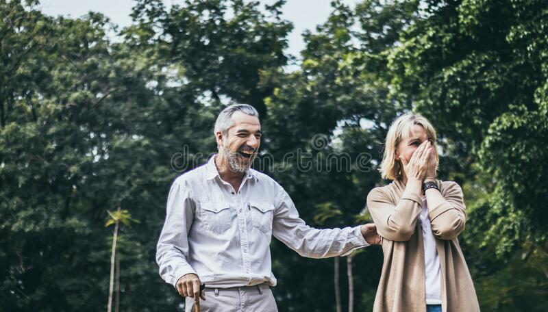 Senior elderly couple man with big laughing and surprised or excited woman in the park. Happy retired life of older people. Marria. Senior elderly couple men stock photo