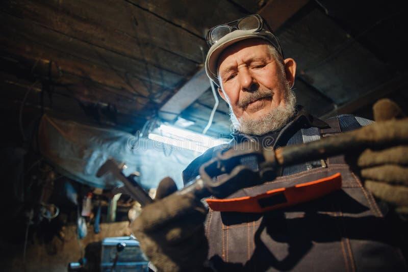 Senior elderly male turner handles metal on machine. Concept pension worker industrial, workplace stock image