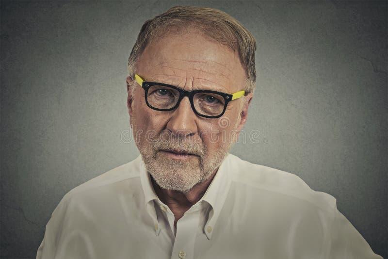 Senior elderly skeptical man with eyeglasses royalty free stock photo