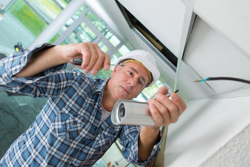 Senior electrician connecting cctv camera in office. Contractor stock images