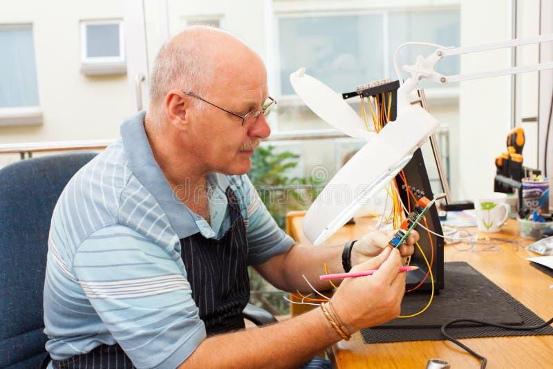 Senior electrician examining stock images