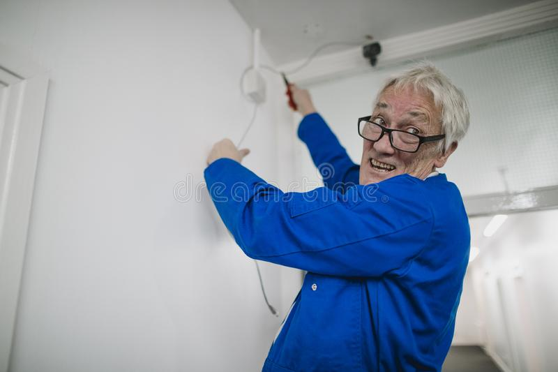 Senior Electrician Fitting a Secuirty Camera royalty free stock image