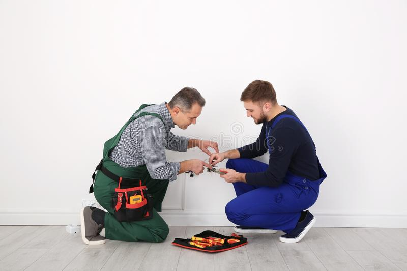 Senior electrician helping trainee stripping wire ends stock photo