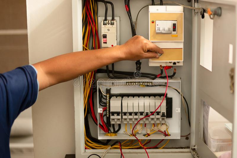 Senior electrician measuring voltage in fuse board. stock images