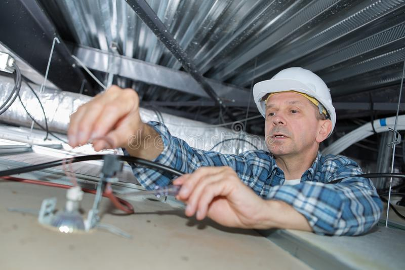 Senior electrician at work in roof space. Electrician royalty free stock image