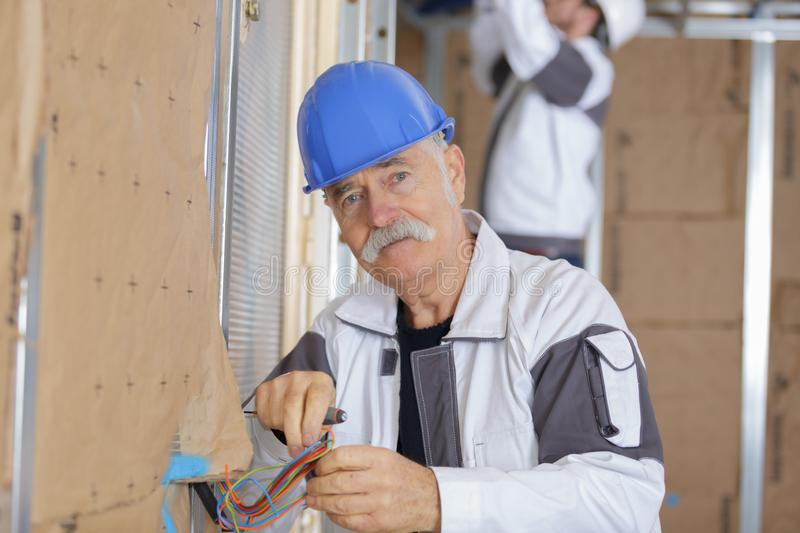 Senior electrician working with wires in new apartment stock images