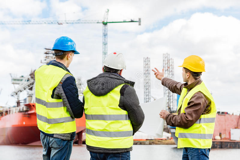 Senior engineer builders at the construction site. Ship building industry. Senior engineer builder at the construction site in a port. Wearing safety helmet and royalty free stock photo