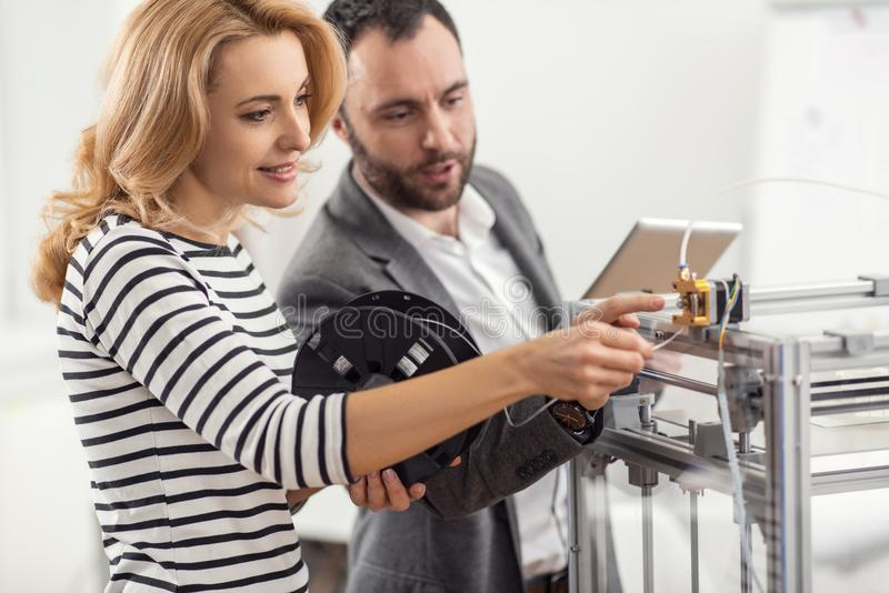 Senior engineer teaching how to insert filament into extruder. Perfect explanation. Charming senior engineer teaching his female colleague how to insert filament royalty free stock photo