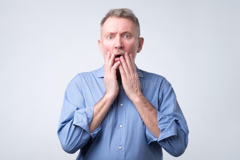 Senior european man with scared and anxious expression, bites finger nails stock photos