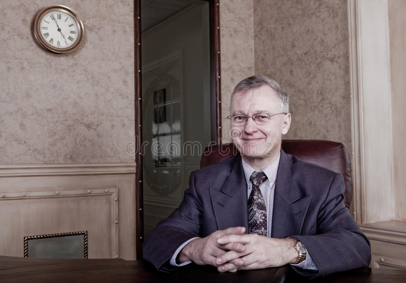 Senior executive anticipating retirement. Anticipation, 5 minutes to retirement royalty free stock photo