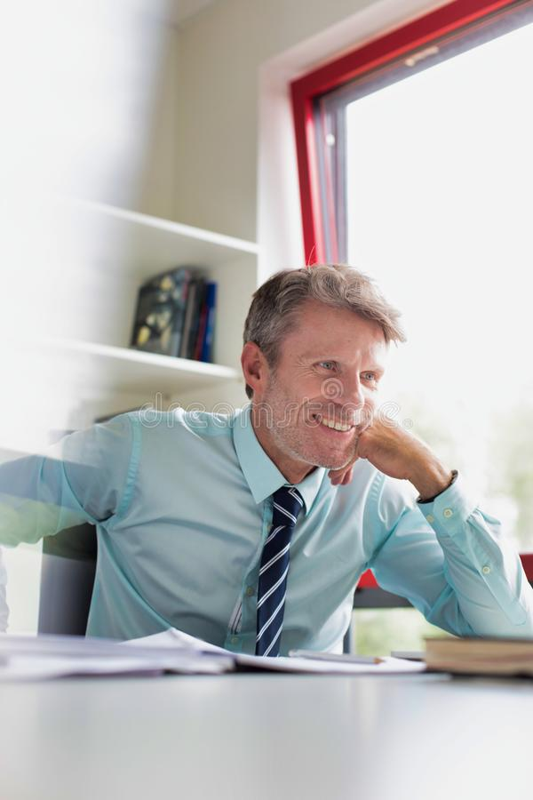 Senior executive business man with his head resting on his hand whilst wearing a suit and tie and smiling in the office stock image