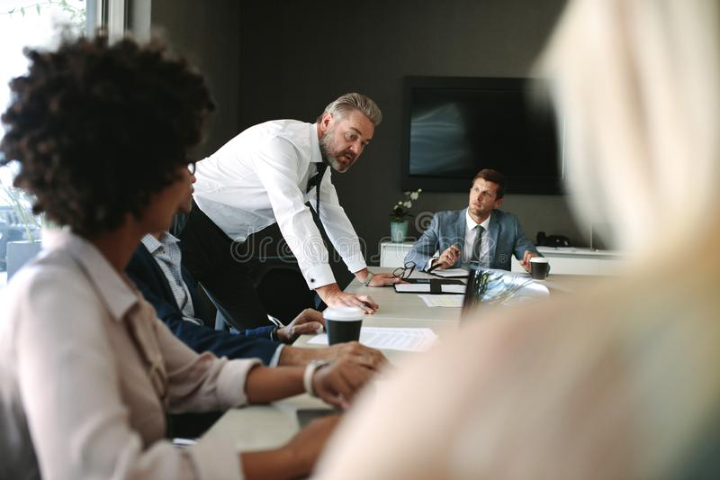 Senior executive explaining something to his team in a meeting stock photos