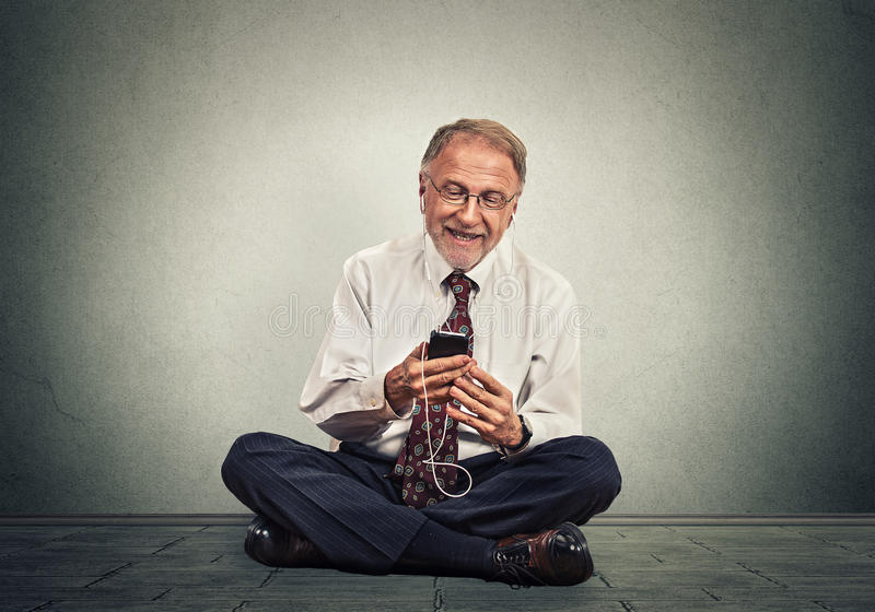 Senior executive man sitting on a floor using smart phone texting listening music royalty free stock photography