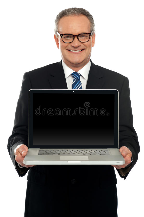 Senior Executive Standing With Open Laptop Stock Image