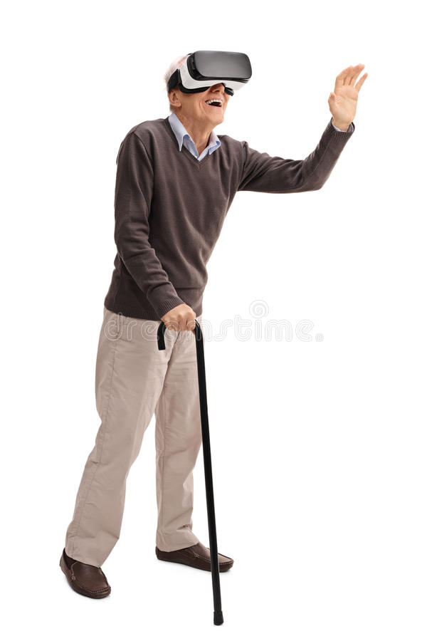 Senior experiencing virtual reality. Full length portrait of a senior with a cane experiencing virtual reality through VR headset isolated on white background stock photography