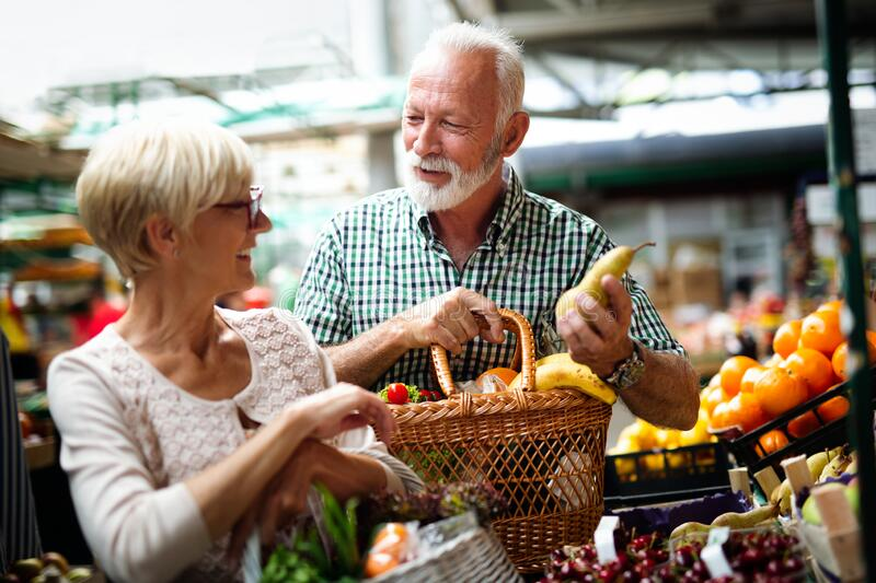Senior family couple choosing bio food fruit and vegetable on the market during weekly shopping stock photos