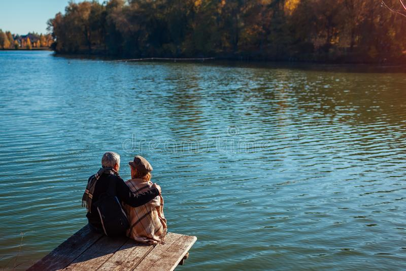 Senior family couple relaxing by autumn lake. Happy man and woman enjoying nature and hugging sitting on pier stock photography