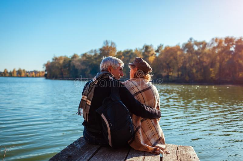 Senior family couple relaxing by autumn river. Happy man and woman enjoying nature and hugging sitting on pier stock photos