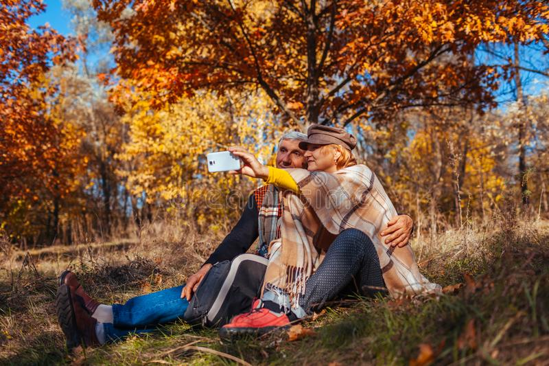 Senior couple taking selfie in autumn park. Happy man and woman enjoying nature and hugging royalty free stock photography
