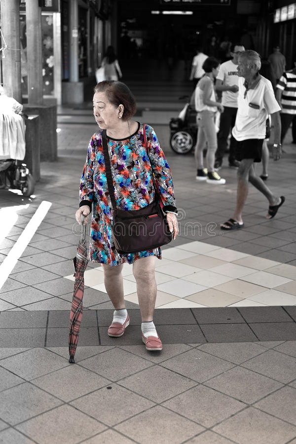 Senior with a fancy dress, MRT Station, Singapore. A candid photograph of a senior lady wearing a colorful and catchy dress at MRT station, Singapore stock images