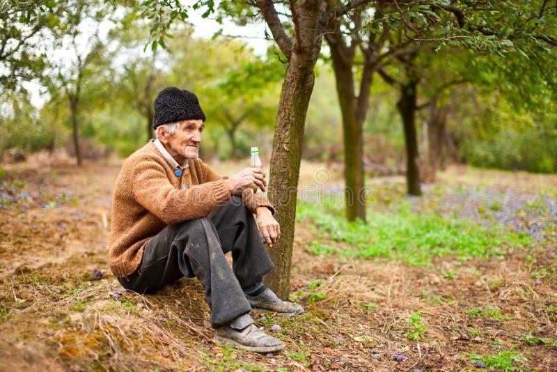 Senior farmer drinking plum brandy