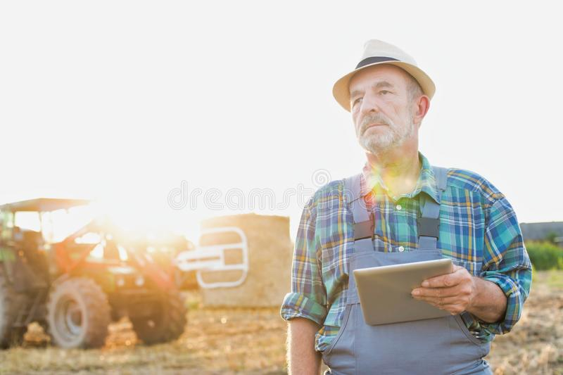 Senior farmer standing with arms corssed against farm tractor, round bale hay in field with yellow lens flare in background. Photo of Senior farmer standing royalty free stock photos