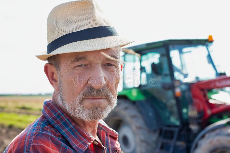 Close up of senior farmer wearing hat while standing against tractor in field royalty free stock images