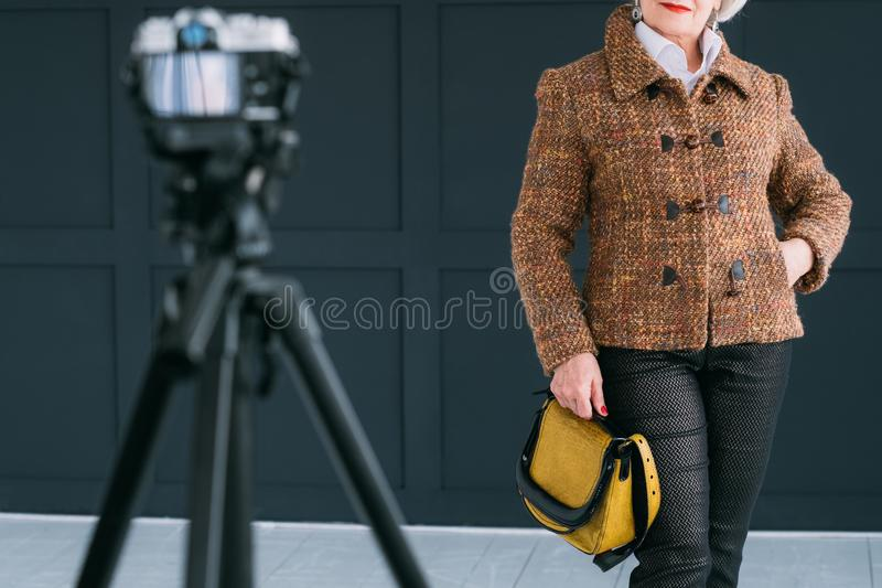 Senior fashion model modern lifestyle photo shoot. Senior fashion model. Modern lifestyle. Stylish aged woman in autumn outfit posing for photo shoot stock images