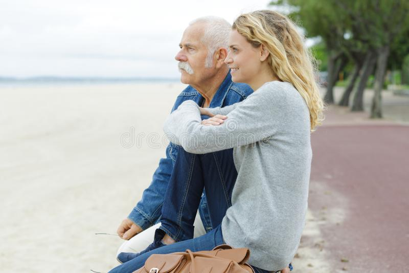 Senior father with adult daughter at sea stock photography
