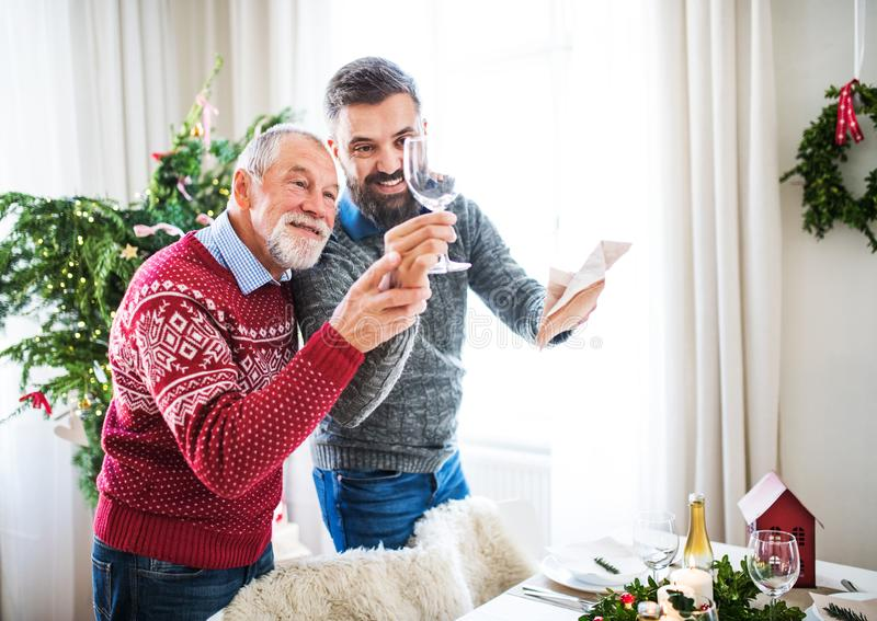 A senior father and adult son setting a table for dinner at Christmas time. stock photos