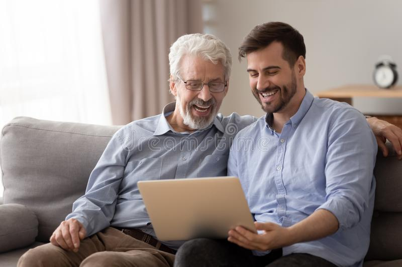 Senior father and adult son using laptop looking at screen. Happy two age generation family senior father and adult son having fun enjoy using laptop at home sit royalty free stock photos