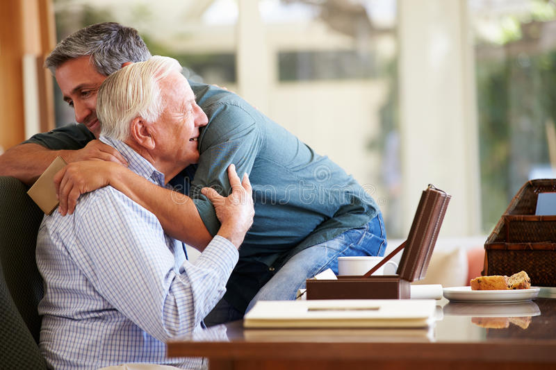 Senior Father Being Comforted By Adult Son. Hugging Each Other royalty free stock images