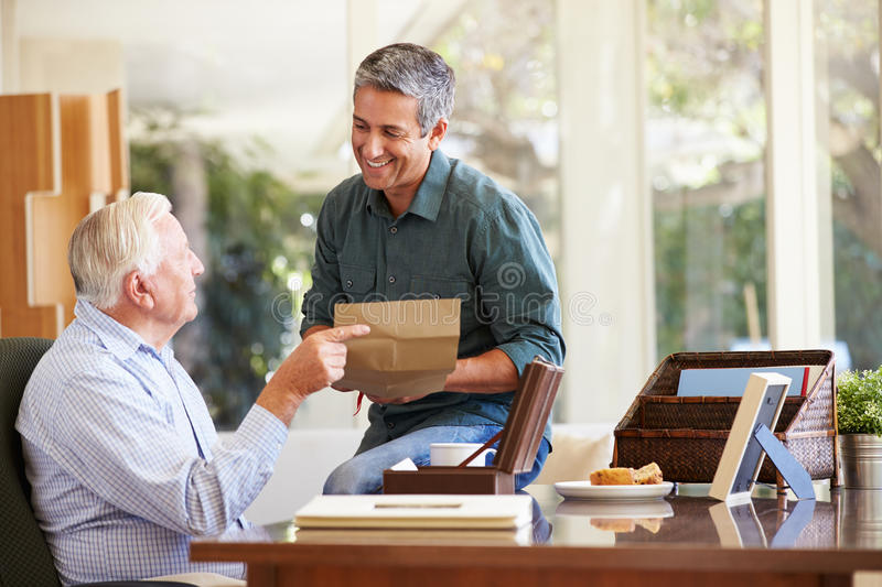 Senior Father Discussing Document With Adult Son. Looking At Each Other Smiling stock photo