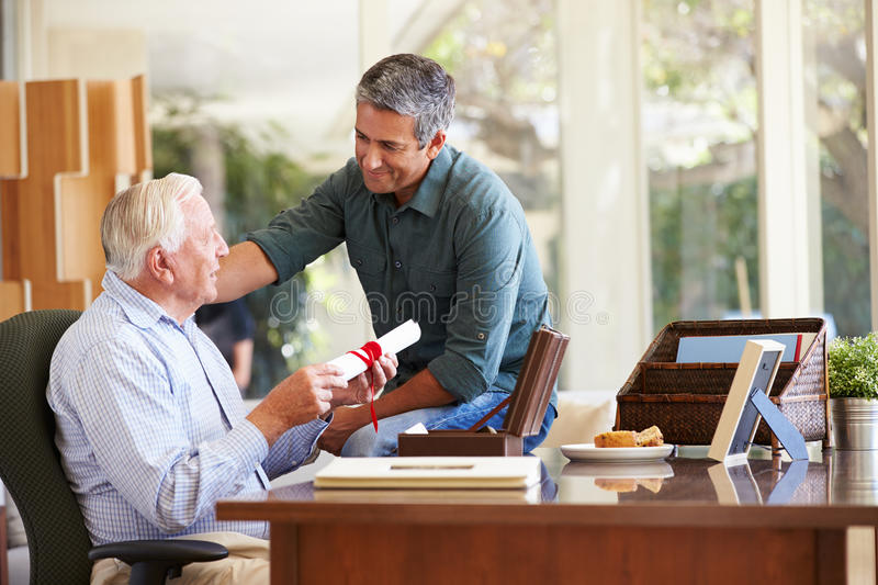 Senior Father Discussing Document With Adult Son. Putting Hand On Shoulder Reminiscing royalty free stock images