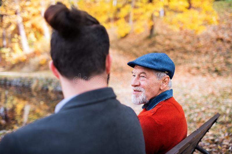 Senior father and his son sitting on bench by lake in nature, talking. Senior father and his young son sitting on bench by lake in nature, talking royalty free stock photos