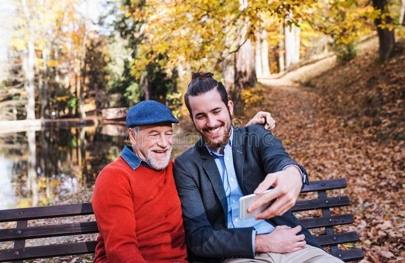 Senior father and his son sitting on bench in nature, taking selfie. royalty free stock images