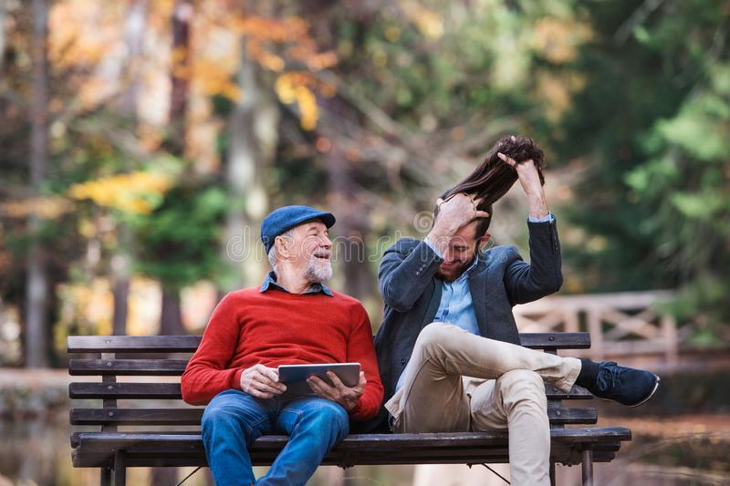 Senior father and his son sitting on bench in nature, using tablet. stock photos