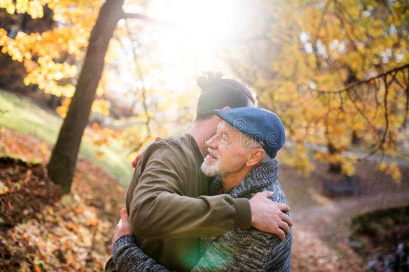 Senior father and his son on walk in nature, hugging. A senior father and his son on walk in nature, hugging at sunset stock images