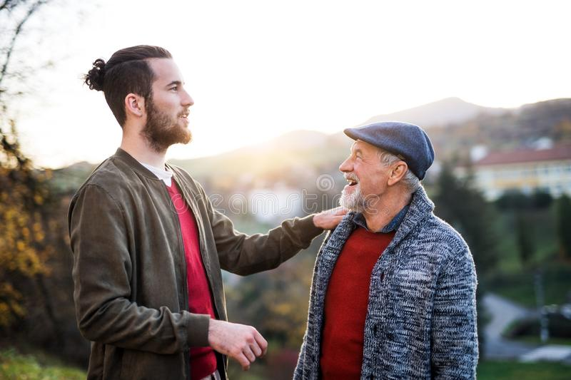 Senior father and his son on walk in nature, talking. Senior father and his young son on a walk in nature, talking royalty free stock photos