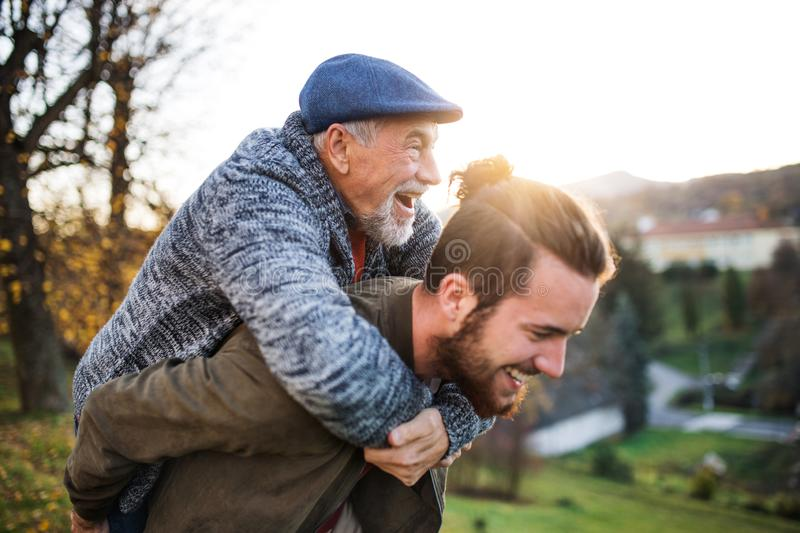 Senior father and his son walking in nature, having fun. Senior father and his young son walking in nature, having fun royalty free stock image