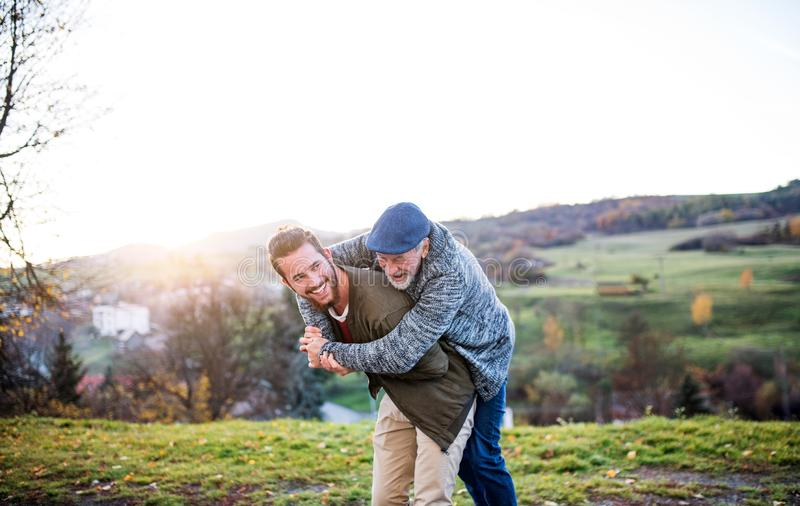 Senior father and his son walking in nature, having fun. Senior father and his young son walking in nature, having fun royalty free stock images