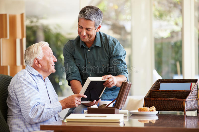 Senior Father Looking At Photo In Frame With Adult Son. Smiling At Each Other royalty free stock photos