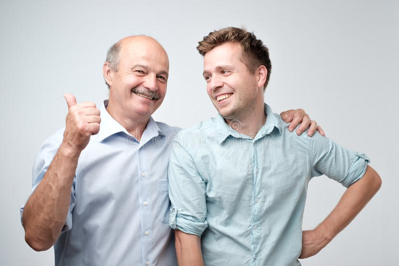 Senior father is proud of his mature son. stock photography
