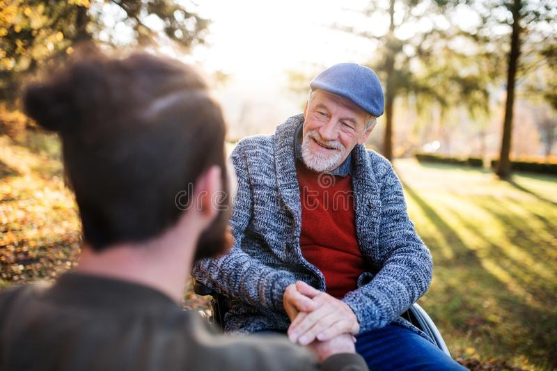 Senior father with wheelchair and his son on walk in nature, talking. A senior father with wheelchair and his son on walk in nature, talking stock photo